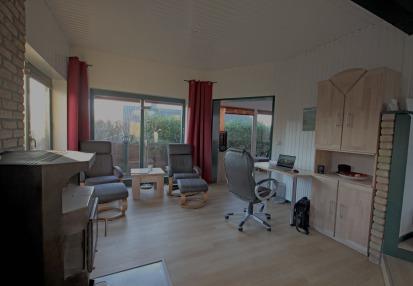 Blick in Wohnzimmer mit Schreibtisch und Relaxsessel